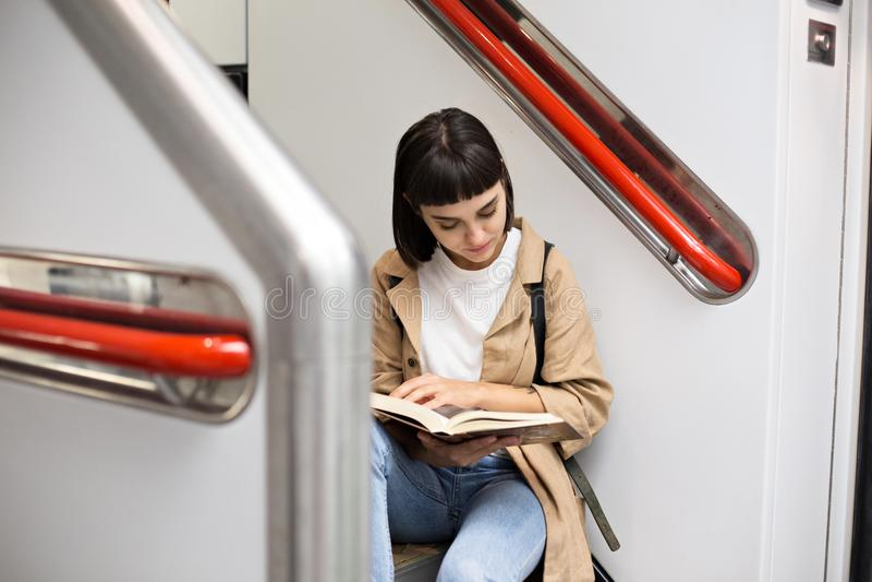 La mujer lee el libro en las escaleras del tren fotografía de archivo libre de regalías