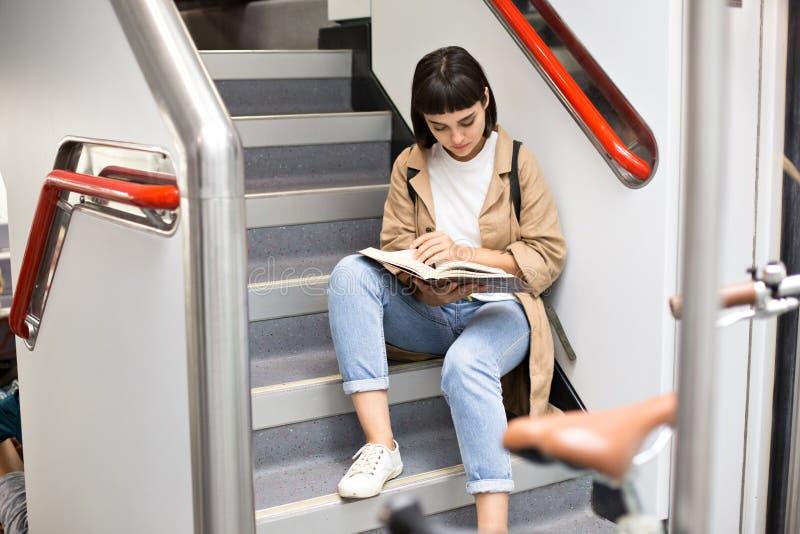La mujer lee el libro en las escaleras del tren imágenes de archivo libres de regalías