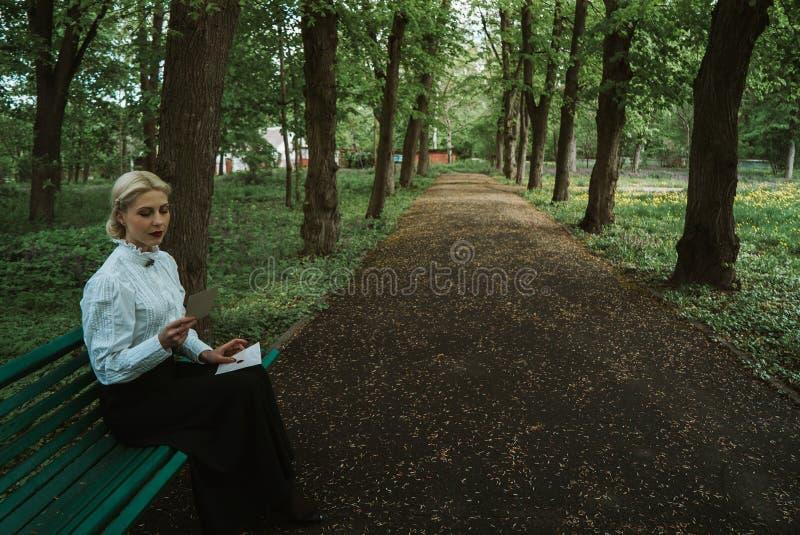 La mujer lee una letra de papel en un banco imagenes de archivo