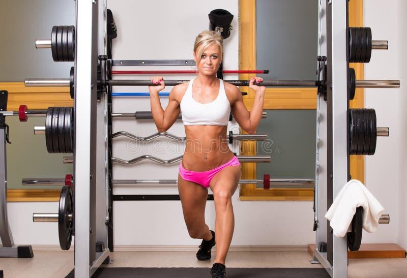 La mujer levanta pesas de gimnasia en centro de deporte para desarrollar los músculos fotografía de archivo libre de regalías