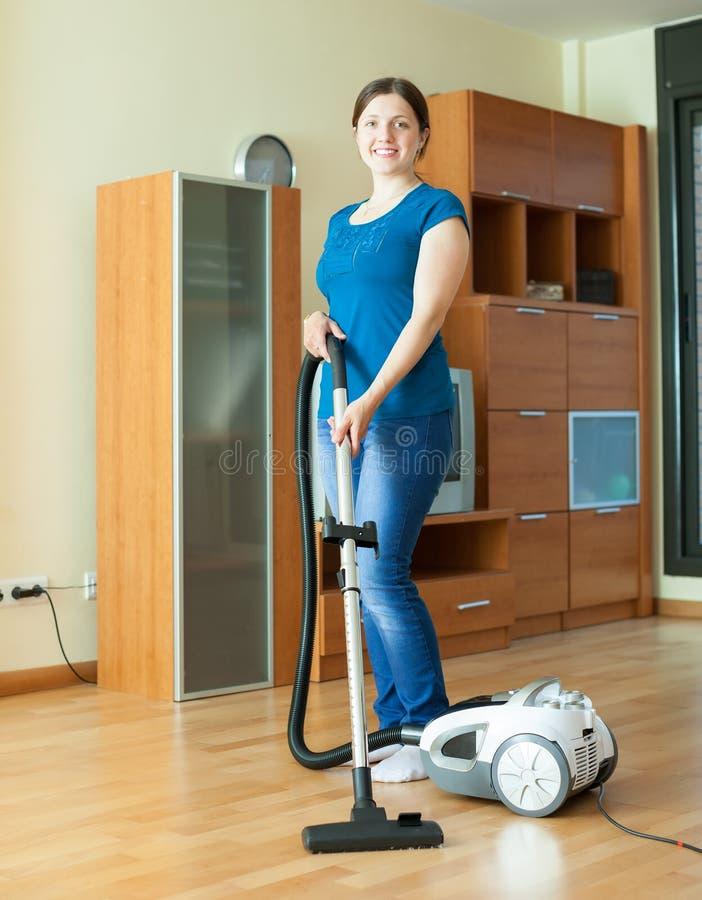 La mujer limpia con el aspirador foto de archivo libre de regalías