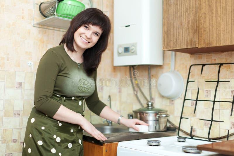 La mujer limpia el fregadero de cocina fotografía de archivo