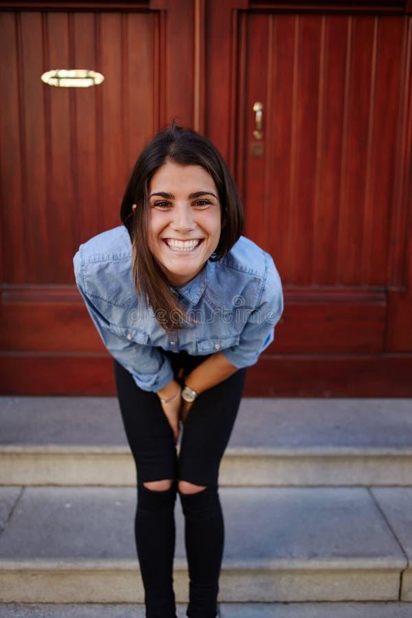 La mujer linda admiringly está sonriendo, modelo femenino encantador que presenta en el fondo de madera de la puerta foto de archivo