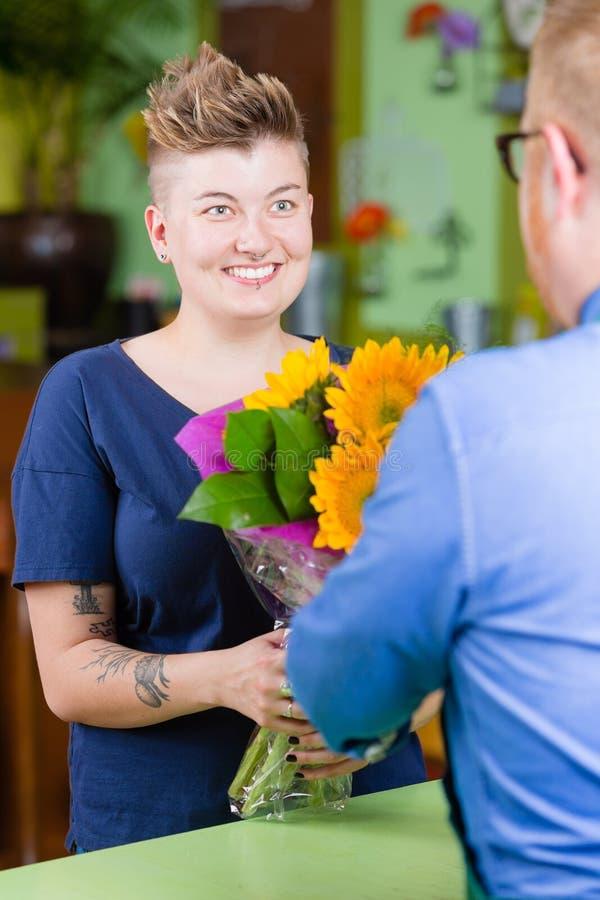 La mujer linda en floristería compra los girasoles fotografía de archivo libre de regalías