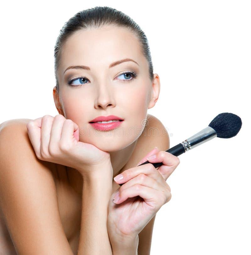 La mujer lleva a cabo el brushe del maquillaje para aplicar el colorete fotografía de archivo libre de regalías