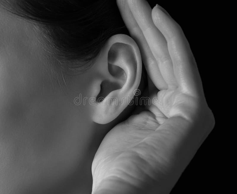 La mujer lleva a cabo su mano cerca del oído foto de archivo libre de regalías