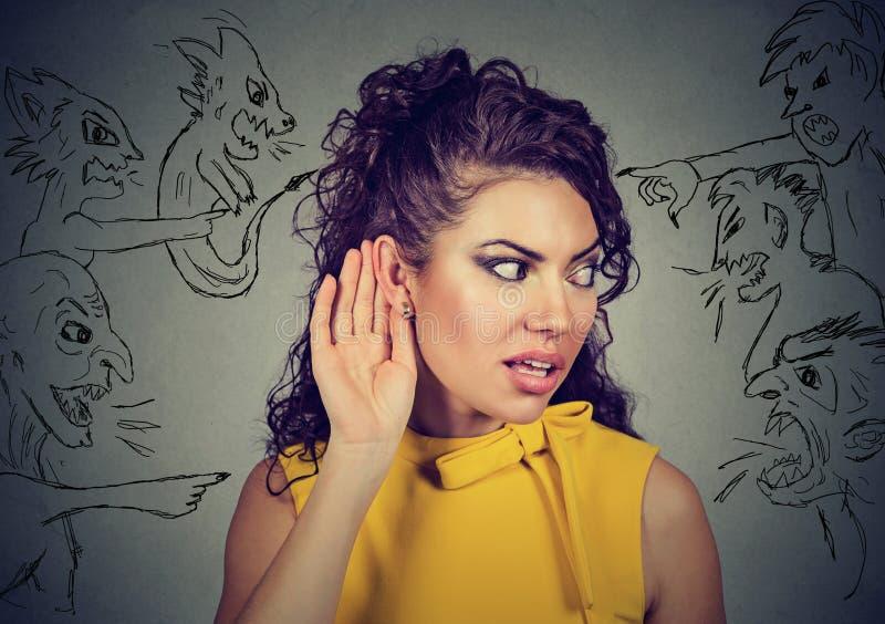 La mujer lleva a cabo su mano cerca del oído y escucha cuidadosamente las voces malvadas fotografía de archivo libre de regalías