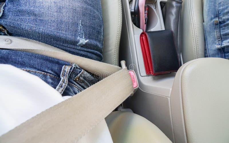La mujer lleva el cinturón de seguridad para la seguridad durante la conducción en el camino foto de archivo