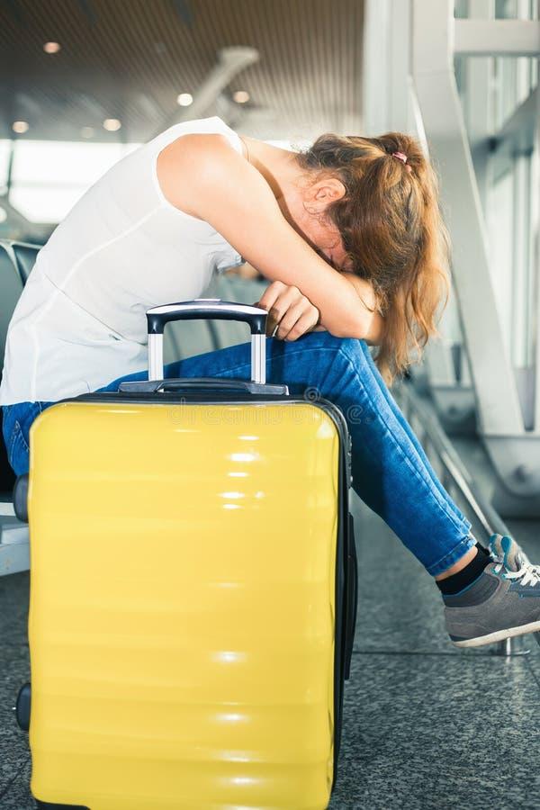La mujer lleva su equipaje en el terminal de aeropuerto imagenes de archivo