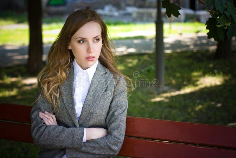 La mujer llorosa se sienta en el banco foto de archivo