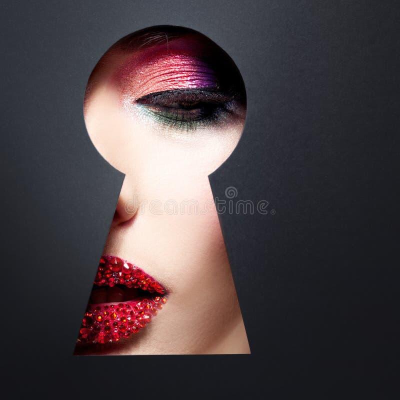 la mujer lujosa joven mira algo secreto en el ojo de la cerradura El concepto de secreto de la belleza, nuevos cosméticos fotos de archivo libres de regalías