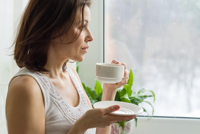 La mujer madura bebe el café de la mañana y mira hacia fuera la ventana en casa Foto en serio femenino del perfil fotos de archivo