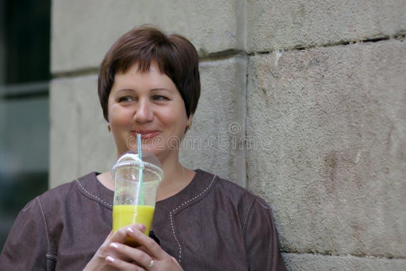 La mujer madura bebe el zumo de naranja foto de archivo libre de regalías