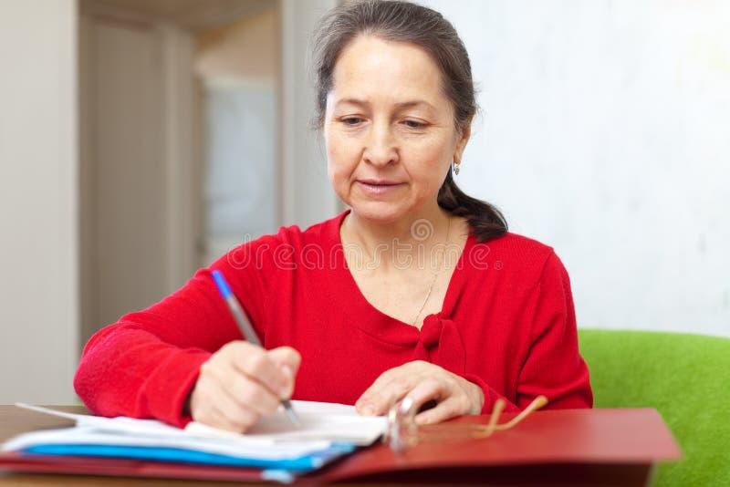 La mujer madura completa el cuestionario imagen de archivo