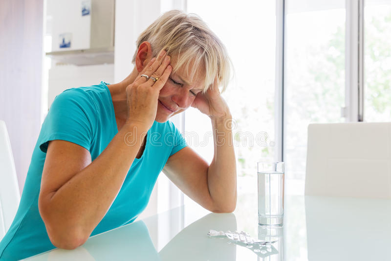 La mujer madura con dolores de cabeza se sienta delante del agua y de las píldoras foto de archivo