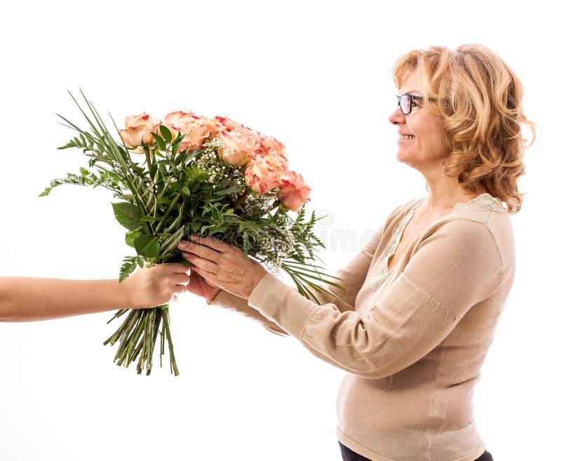 La mujer madura consigue el ramo de rosas, día del ` s de la madre foto de archivo