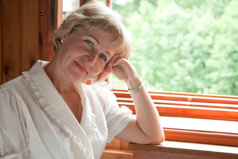 La mujer madura en la ventana abierta foto de archivo