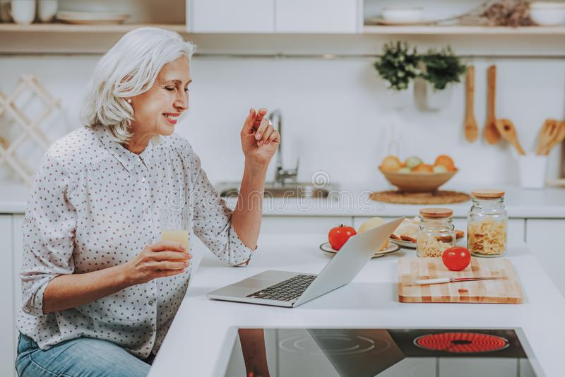 La mujer madura feliz está mirando el ordenador portátil durante cocinar en casa fotografía de archivo