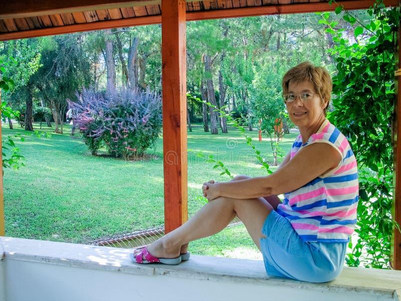 La mujer madura hermosa con los vidrios se sienta en la cerca de piedra en Garde foto de archivo libre de regalías