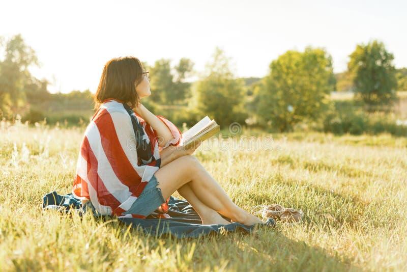 La mujer madura lee un libro, restos en la naturaleza En la bandera americana de los hombros, puesta del sol del fondo, paisajes  foto de archivo