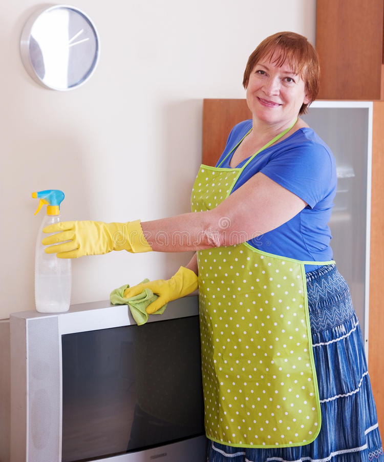 La mujer madura limpia la casa fotografía de archivo libre de regalías