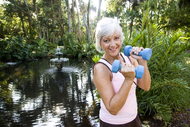 La mujer madura que ejercita en mano de elevación del parque pesa foto de archivo libre de regalías