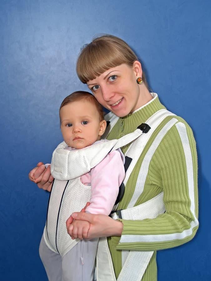 La mujer mantiene al bebé una honda del bebé fotografía de archivo libre de regalías