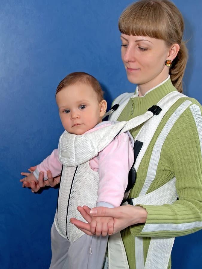 La mujer mantiene al bebé una honda del bebé imágenes de archivo libres de regalías