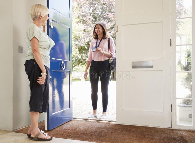 La mujer mayor abre la puerta en el trabajador de sexo femenino del cuidado en la visita casera fotografía de archivo libre de regalías