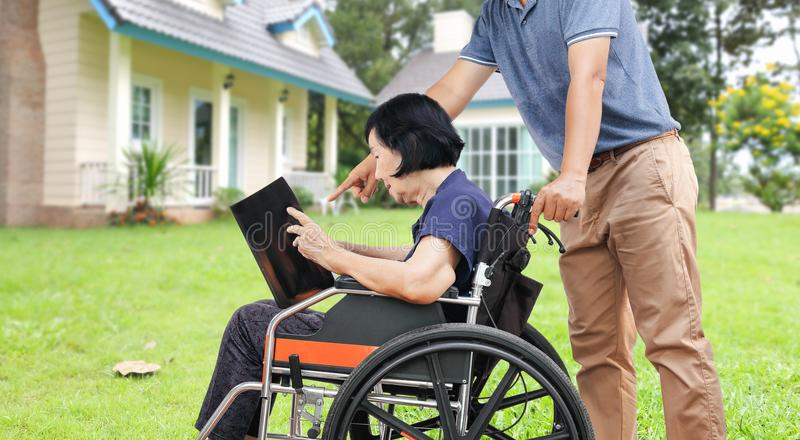La mujer mayor asiática que lee un libro con su hijo toma cuidado en el CCB imágenes de archivo libres de regalías