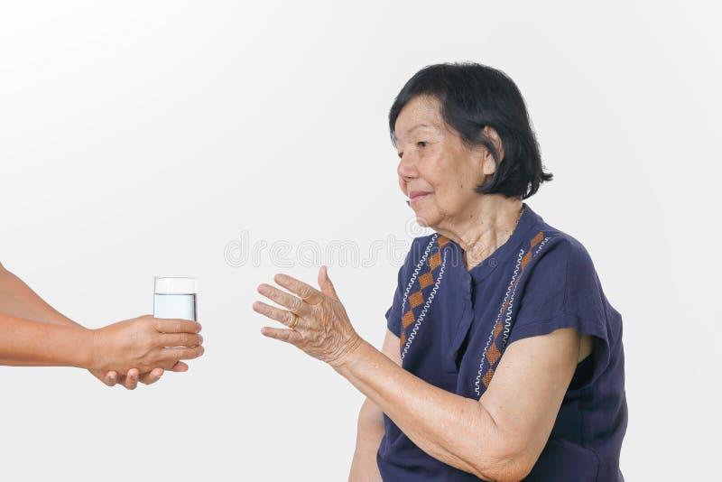 La mujer mayor consigue un vidrio de agua de cuidador fotografía de archivo libre de regalías
