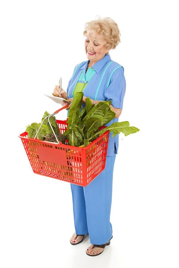 La mujer mayor controla la lista de compras imagenes de archivo