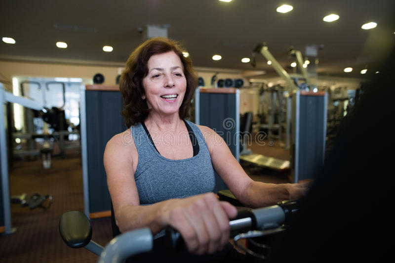 La mujer mayor del ajuste hermoso en hacer del gimnasio cardiio se resuelve imagen de archivo