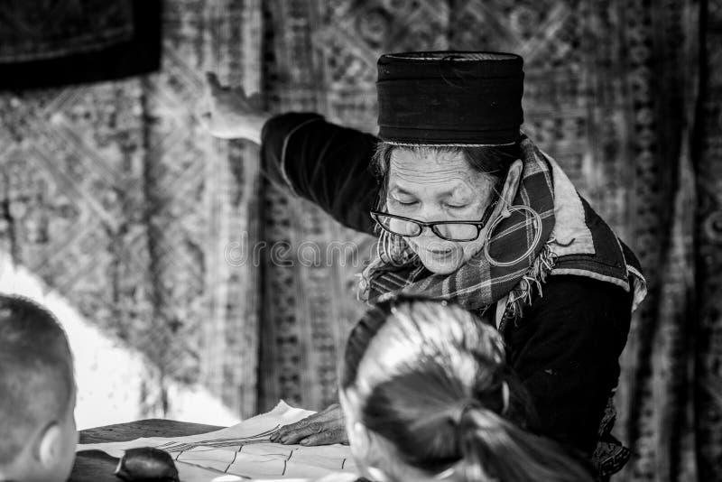 La mujer mayor del nombre de la tribu de Hmong está pintando encendido a la tela blanca foto de archivo