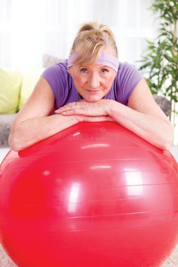 La mujer mayor después de ejercicios se relaja imagen de archivo