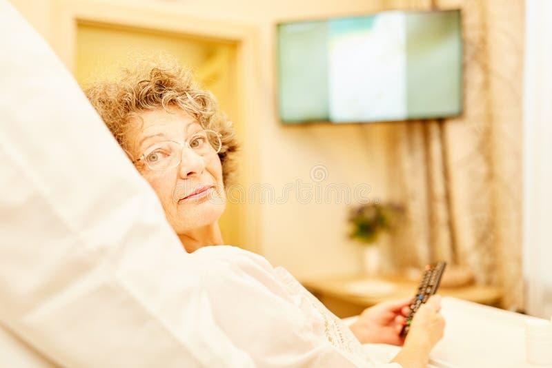 La mujer mayor en casa de retiro está mintiendo en cama imagen de archivo libre de regalías