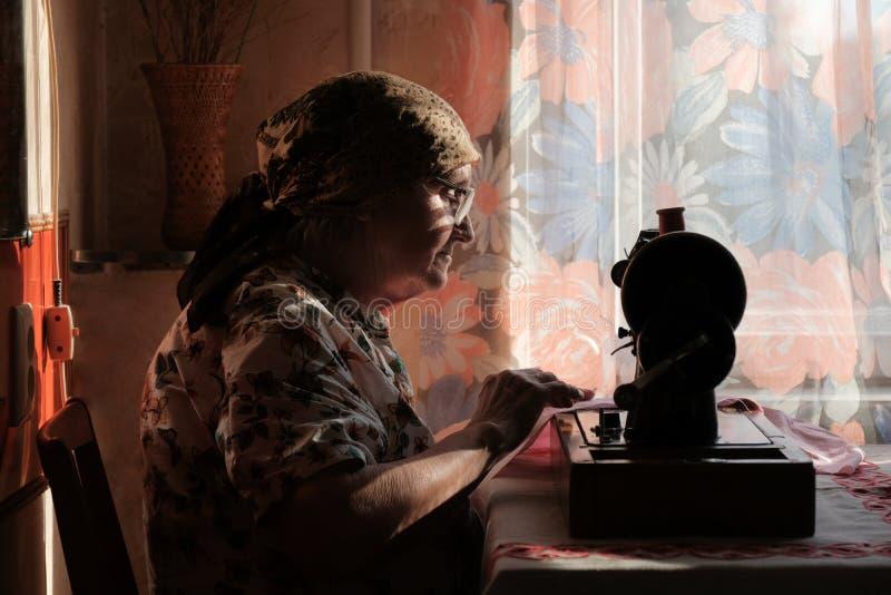 La mujer mayor en gafas utiliza la máquina de coser, silueta de la vieja modista fotos de archivo libres de regalías