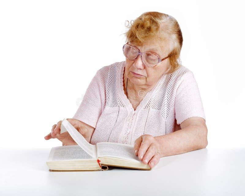 La mujer mayor en vidrios lee el libro en un blanco imagenes de archivo