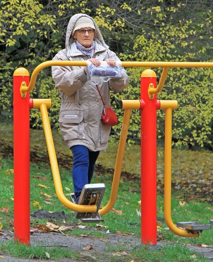 La mujer mayor está ejercitando en el parque de la ciudad de Varsovia fotografía de archivo libre de regalías