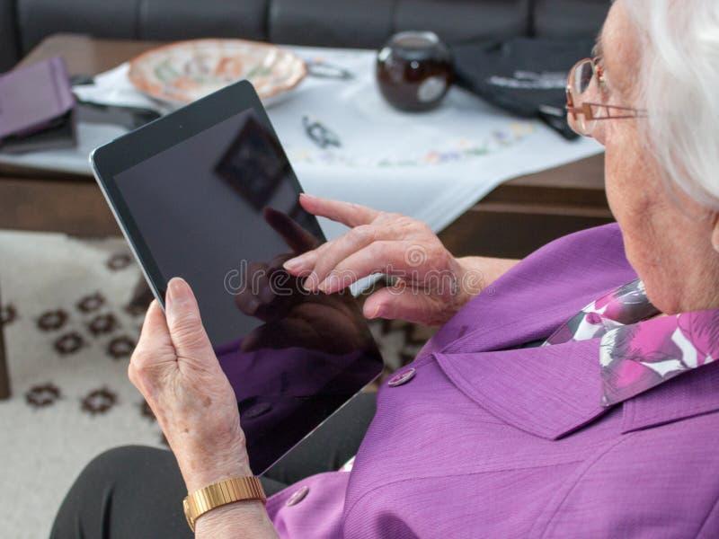 La mujer mayor está mecanografiando en una tableta fotos de archivo