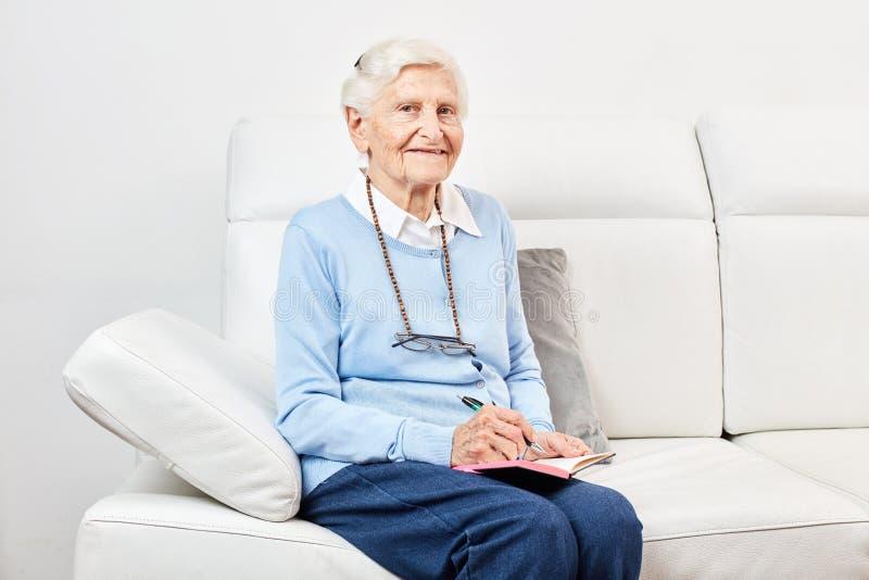 La mujer mayor feliz se está sentando en el sofá fotos de archivo libres de regalías