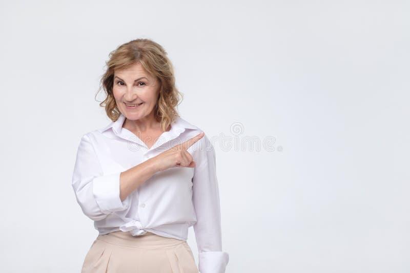 La mujer mayor hermosa en la camisa blanca está señalando al lado, mirando la cámara y la sonrisa imagenes de archivo