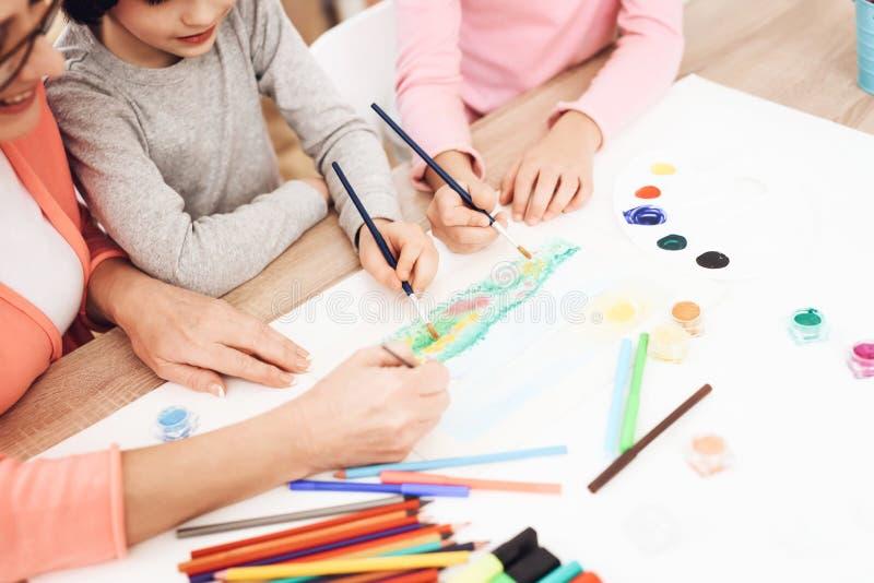 La mujer mayor hermosa enseña a niños a dibujar Drenaje de los pequeños niños Lecciones del dibujo foto de archivo