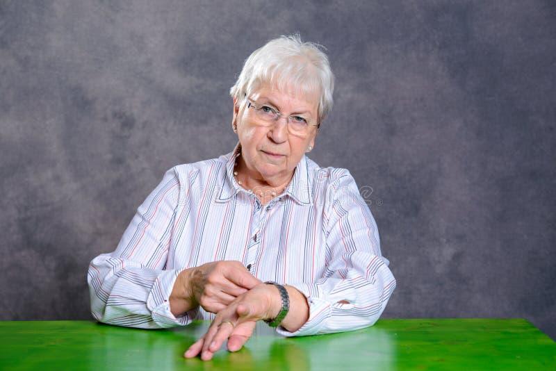 La mujer mayor melenuda gris fijó su reloj imagenes de archivo