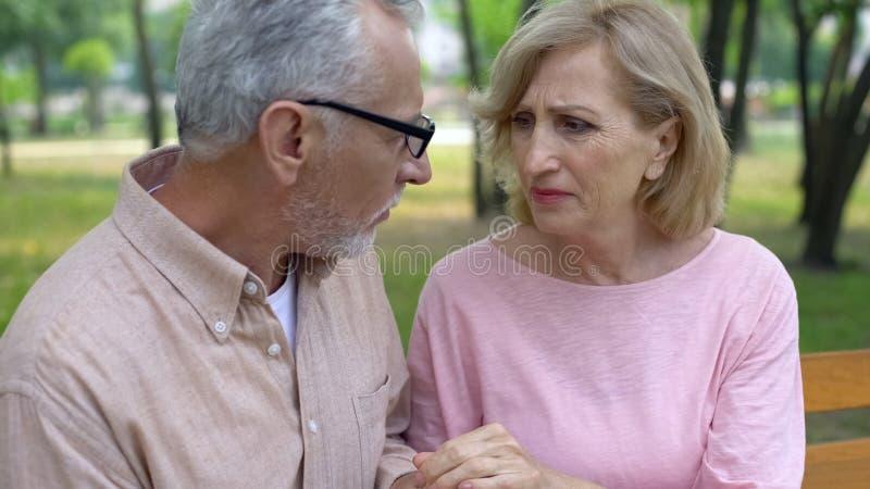 La mujer mayor presionada que mira al marido, llevando a cabo las manos, las relaciones apoya imagenes de archivo