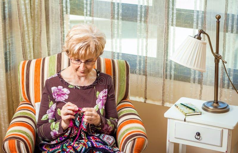 La mujer mayor que hace punto una lana acolcha con los remiendos imagen de archivo