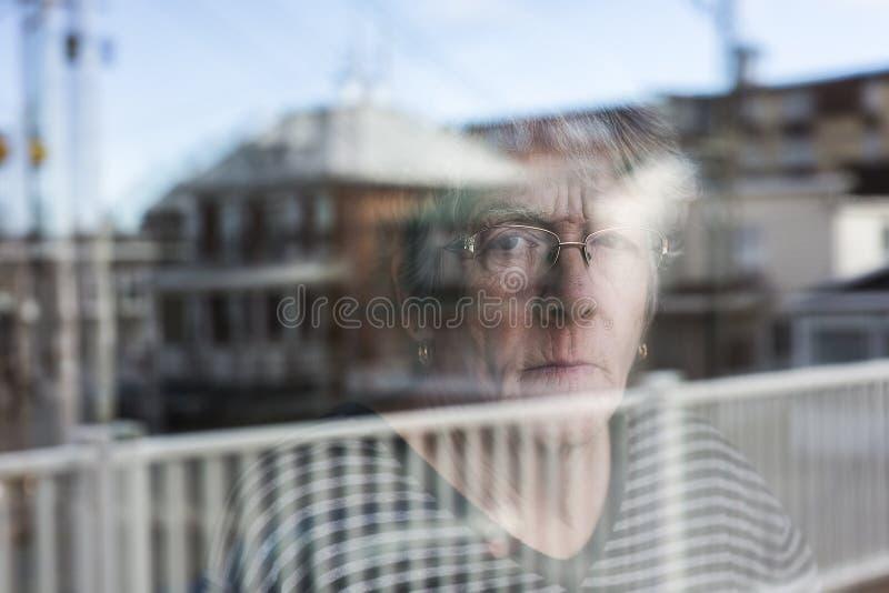 La mujer mayor que mira hacia fuera a través de una ventana como presiona imagen de archivo libre de regalías