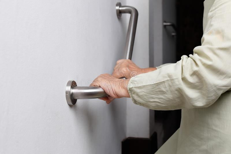 La mujer mayor que sostiene encendido la barandilla para la seguridad camina fotografía de archivo