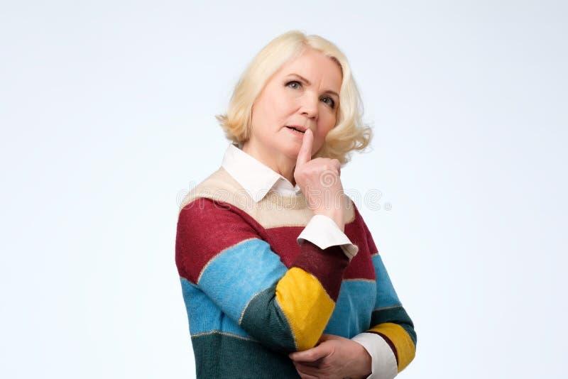 La mujer mayor que tiene rato dudoso de la mirada no puede decidir qué elegir fotografía de archivo