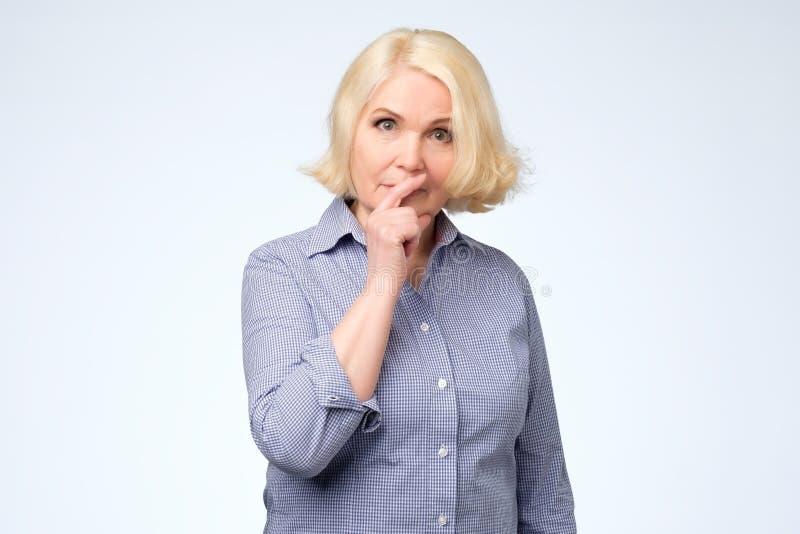 La mujer mayor que tiene rato dudoso de la mirada no puede decidir qué elegir imagenes de archivo
